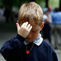Un enfant fait son signe de croix