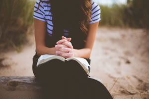 Jeune femme qui prie avec bible par Ben White (unsplash.com)